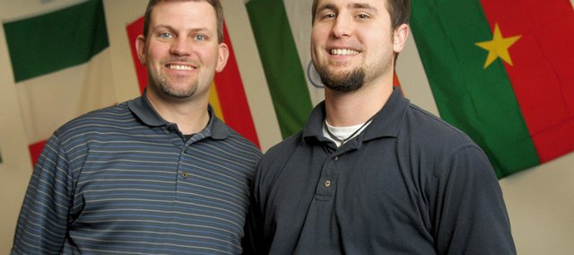 New Creation Church pastor Jason Haskell, left, and Jon Curtis stand in front of the international flags displayed in the church's sanctuary. The flag on the right belongs to Burkina Faso, an African country Haskell and Curtis will visit next month with five other church members.