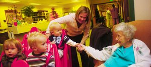 One-year-old Branson Boyce shakes hands with Doak Walker Care Center resident Lila Rider on Thursday morning when children enrolled at the neighboring GrandKids Child Care Center visited residents. Tentative plans call for relocating the nursing home about two miles from the hospital on the southern edge of Steamboat Springs.