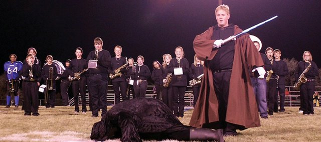 Keath Fenton, Moffat County High School marching band drum major, dressed as Anakin Skywalker, takes out Darth Maul, played by MCHS assistant principal Travis Jensen, during the opening of the band's homecoming half-time show Friday night.
