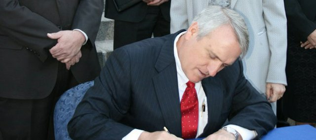 Gov. Bill Ritter signs Colorado House Bill 10-1365, also known as the Clean Air, Clean Jobs Act, on Monday on the steps of the state capitol surrounded by supporters. Several local officials, including the Moffat County Commission, opposed the bill, claiming it would hurt the Northwest Colorado coal industry.