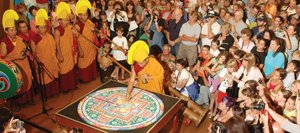 A member of the Drepung Loseling monks begins the transformation of the compassion Buddha mandala before more than 300 intensely curious onlookers in Library Hall at Bud Werner Memorial Library on Wednesday night. The program continued with a short parade on 13th Street and a riverside ceremony.