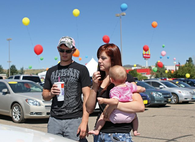 Tim Turner, left, and his wife, Rachelle, holding their 7-month-old daughter, Abigail, look at a sports utility vehicle during a vehicle tent sale Tuesday in the Kmart parking lot. The sale features used vehicles from Grand Valley Auto in Grand Junction. Local dealers say organizers of such events have no accountability to customers once they've made a sale.