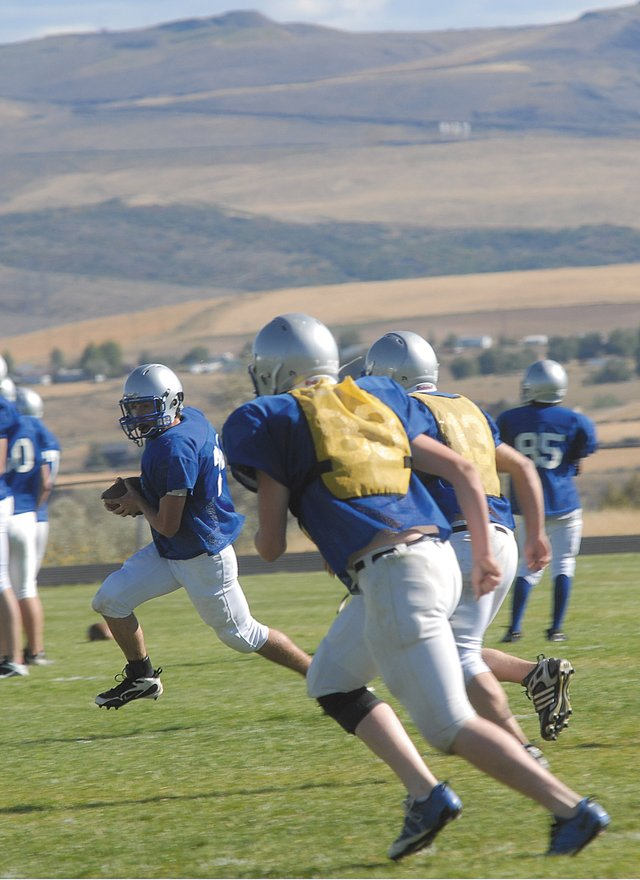Sophomore Ryder Seely, shown here carrying the ball, tries to outrun a pair of scout team defenders Friday during Moffat County High School varsity football practice. The Bulldogs had a bye week this week, but will resume its grueling 10-game schedule Sept. 17 when John F. Kennedy High School comes to Moffat County.