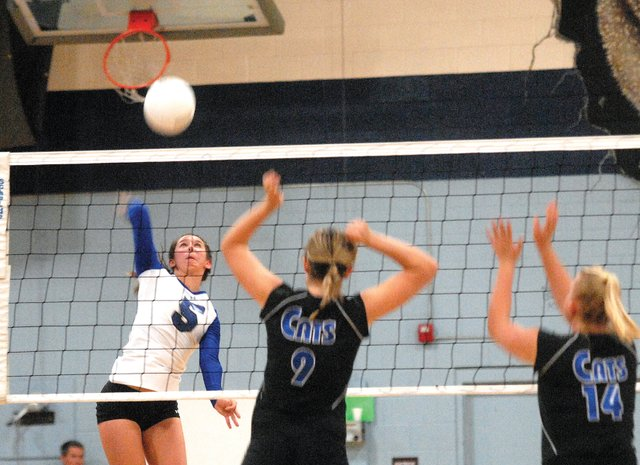 MCHS senior Kelley Syvertson, left, spikes the ball Saturday against the visiting Fruita-Monument Wildcats. The Wildcats won the match, three games to none.
