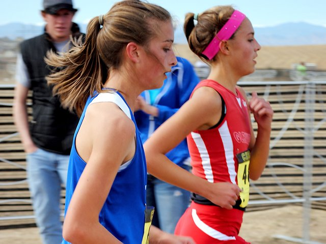 Moffat County High School freshman Brenna Ciesco races next to an opponent from Glenwood Springs during Saturday's Colorado State High School Cross Coutnry Championships on Saturday. Ciesco finished 34th in the race. The girls team finished 12th.
