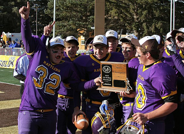 Jacob Ready, left, a sophomore LSRV Rattler, leads his team in celebration as they hoist the Wyoming six-man state championship trophy Friday in Laramie, Wyo.