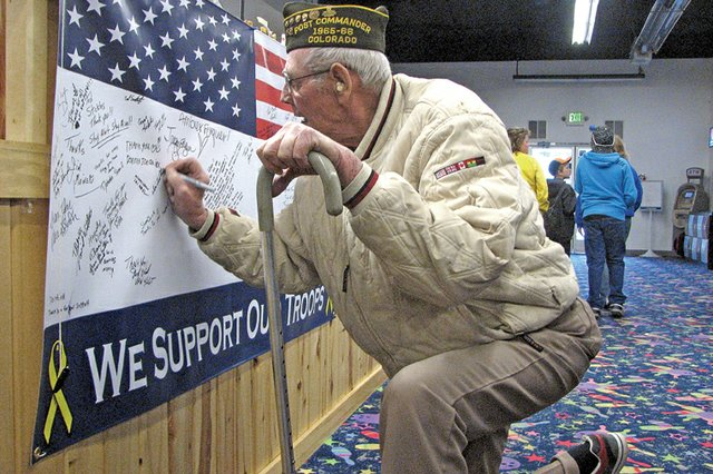 U.S. Marine Corps veteran Alvin Lawton, who served in Korea from 1952 to 1954, signs his name to a banner Saturday at Thunder Rolls Bowling Center in Craig. The banner is in support of U.S. troops. During the past month, Thunder Rolls has raised more than $2,500 for the Bowlers to Veterans link, an organization that provides support to former and active servicemen and women.
