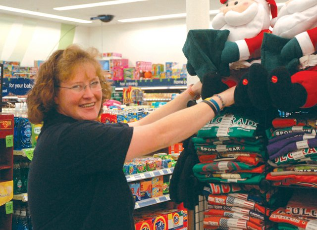 Walgreens service clerk Donna Aldridge positions a stuffed Santa Claus with the rest of the store's holiday decorations. Aldridge has worked at Walgreens for two years. In her spare time, she likes to go mud-bogging, hunting and camping, playing pool with her family, and spending time with her numerous pets.