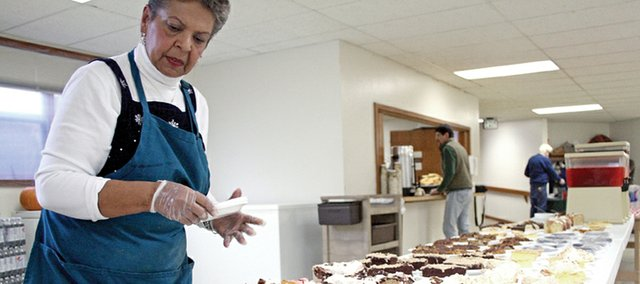 Craig resident Marge McKenzie arranges desserts during a benefit dinner Saturday at St. Michael Catholic Church. McKenzie's daughter, DeAnna Jacobs of Petersburg, N.Y., suffers from autonomic neuropathy. McKenzie organized the dinner to raise money for an extended stay with Jacobs in New York.