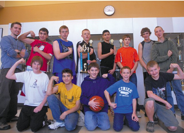 The members of the Craig Middle School eighth-grade boys basketball A team flex their muscles in celebration of the team's first-place victory at last weekend's district tournament. The team beat Rangely and Steamboat Springs to finish a perfect 14-0 season.