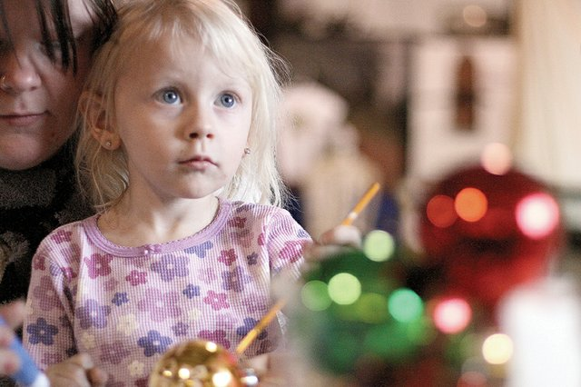 Shelby Wilson, 3, paints a Christmas ornament Saturday with a little help from her mother, Jessica Seales. The two were at the third annual Christmas for Kids event at Wyman Museum.