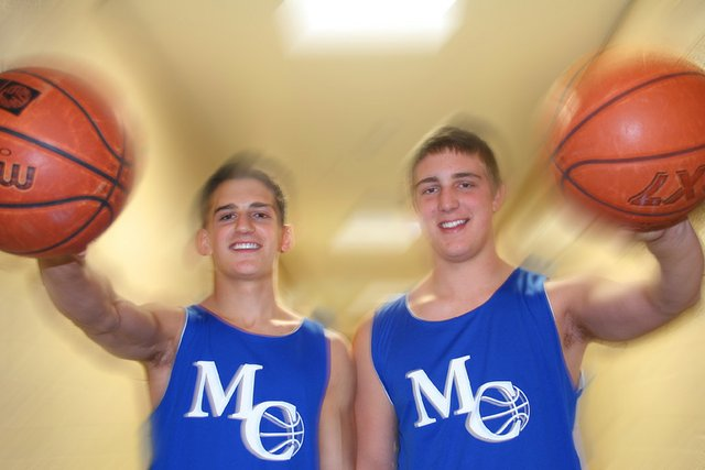 Zach Raftopoulos, left, and Angelo Raftopoulos palm a pair of basketballs during a practice session. The two cousins are expected to start this season on the varsity team.