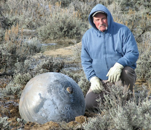Robert Dunn stands next to a pressurant tank he discovered March 21 in Moffat County while looking for deer and elk horns. NASA spokesman William Jeffs said the tank is from a Russian rocket that reentered March 19.