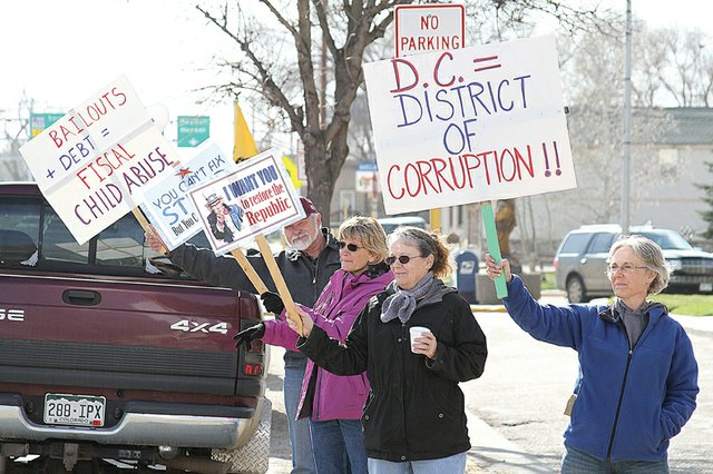 Meeker resident Patti Hoke, right, holds up a sign in protest Friday at the 2011 Tax Day Freedom Rally hosted by the Bears Ears Tea Party Patriots at the Moffat County Courthouse. About 100 residents from the area including Rangely, Baggs, Wyo. and Steamboat Springs attended the event, which featured speakers, music and prizes.