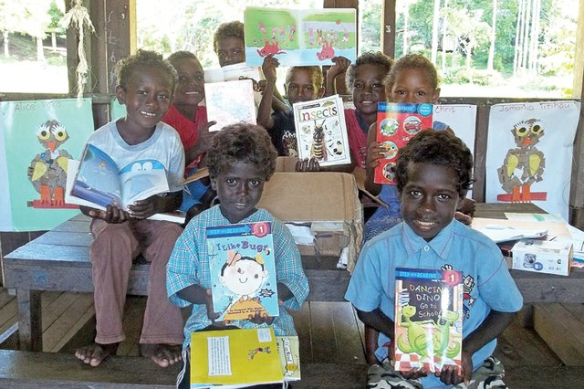 First-grade students at Chukopi Primary School in the Solomon Islands pose June 16 with books they received from Craig students.  In January, students in Sheryl Spears' first-grade class at Sunset Elementary School shipped more than 75 books, school supplies and a digital camera to their sister school in the South Pacific.