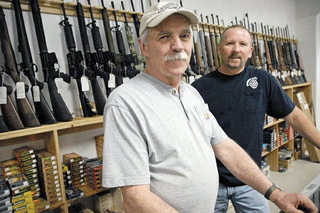 Jim Hixson, left, and Jeff Knights stand Friday behind the counter at Northwest Pawn Shop, a business Knights has owned for six years. The shop sells new and used guns, archery supplies, tools and more. The pawn side of the business can help people out of a tight financial spot, they said.