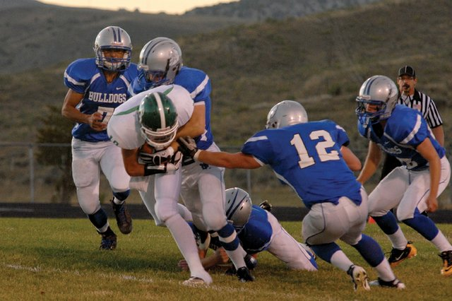 Multiple Moffat County High School varsity football players converge to tackle a Delta High School player Friday at MCHS. After a slow start to the season, the Bulldogs' defense held their own against the Panthers to give MCHS their first win of the season, 22-14.