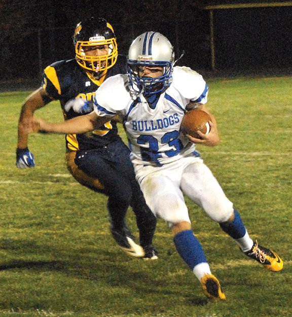 Moffat County High School junior Garrett Stewart runs the ball with Rifle High School sophomore Javier Nunez close behind in Friday night's game in Rifle. The Bulldogs failed to score an offensive touchdown while falling to the Bears, 48-6.