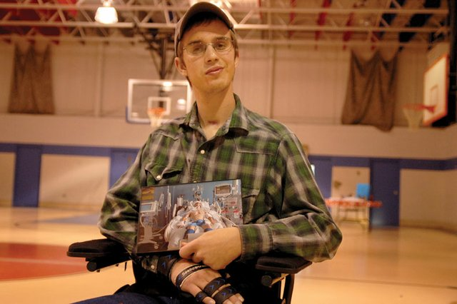Steven Sharp, 21, sits in a wheelchair Sunday at the Boys &amp; Girls Club of Craig holding a picture of himself on life support at St. Marys Hospital in Grand Junction. Sharp spent six months in the hospital after a June 26 motocross crash caused traumatic brain injuries. He returned home Sunday, and friends and family hosted a reception to welcome him back.