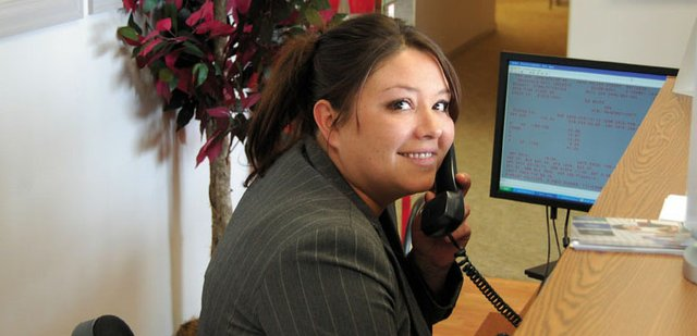 Haley Brumback fields a call at the front desk of Bob Johnson Insurance Agency, 690 W. Victory Way. Brumback, 33, a Craig native, recently began working at the State Farm affiliate after moving back to town with her teenage son.