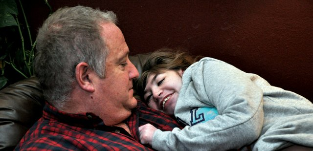 Katelynn Hildebrandt, 16, smiles at her father, Todd, as he prepares to feed her early one morning in mid-February. Because Katelynn is legally blind and deaf and cannot speak, her parents may never know how much of the world she perceives or understands, yet she expresses her affection for them during the most routine acts of the day.
