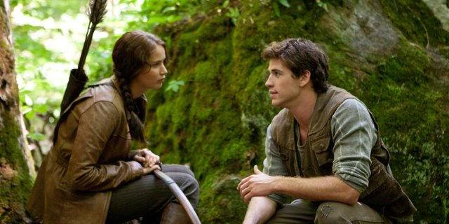 "Katniss Everdeen (Jennifer Lawrence), and her friend Gale (Liam Hemsworth) reflect on their lives while hunting in the forest in ""The Hunger Games."" The movie, based on the book by Suzanne Collins, is about two teenagers selected to fight to the death against 22 other young people as part of a ritual in their country."