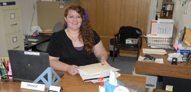 Amanda Boyd, a secretary at AccuComp Accounting, shuffles through paperwork the day before the April 17 income tax deadline. Boyd, 25, was born and raised in Craig and has also worked with her family in the long-standing local business, Ike & Son Transmission & Auto.