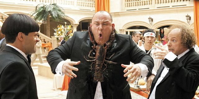 Curly (Will Sasso) finds himself on the wrong end of a seafood dinner at a high society function, much to the amusement of pals Moe (Chris Diamantopoulos) and Larry (Sean Hayes) in The Three Stooges. The movie is a recreation of the classic comedy team, focusing on the Stooges as they set out to save their childhood orphanage.