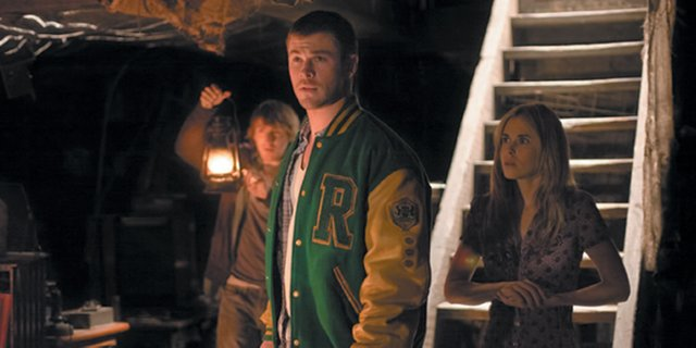 "From left, college students Marty (Fran Kranz), Curt (Chris Hemsworth) and Jules (Anna Hutchison) cautiously walk into the darkness of the creepy cellar of their vacation retreat in ""The Cabin in the Woods."" The movie is about five young people who find themselves involved in a deadly ritual when they travel to a remote nature location."