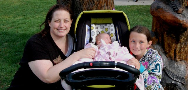 Julie Gates, left, and her daughters, Jayce, 10 weeks, and Joey, 9, walked Saturday afternoon among the woodcarvings in Veterans Memorial Park. Julie, 35, said her favorite part of motherhood is watching her children grow and spending as much time with them as possible.