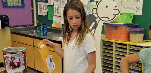 "Third-grader Gabrielle Ellis looks at the assortment of paper ""pets"" Monday at The B.Y.L. Pet Shop in Julie Sperl's classroom at Sandrock Elementary School. Students made and sold goods in shops as part of Kid Town, a unit designed to shed light on economics and democratic government."