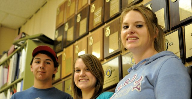 From left, Brady Martinez, Emily Wellman and Makayla Goodnow, members of the Moffat County High School Future Farmers of America meat judging team, pose for a photo Tuesday at the high schools agricultural shop. Their team, which included MCHS junior Tyler Hildebrandt, took the state title in meat judging during an FFA event April 30 in Fort Collins.