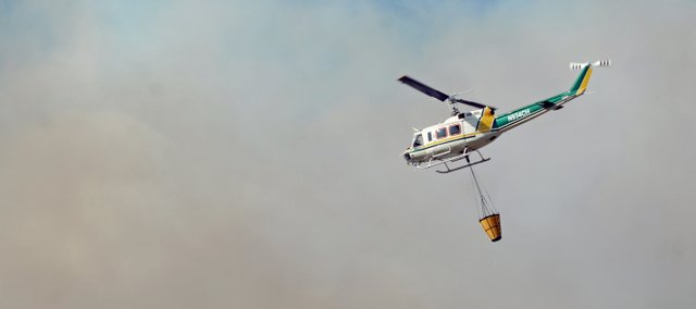 A Bureau of Land Management helicopter equipped with a scoop responds to a report of a wildfire off U.S. Highway 40 near mile marker 79 in Moffat County.