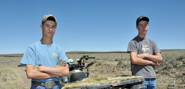 Tyler Gerber, 15, left, and his brother Kearn, 14, stand near a four-wheeler they used Wednesday to repair fence on the family ranch after Tuesdays Sand Fire about 10 miles west of Craig. Tyler saw the blaze soon after it ignited, and he was praying that it wouldnt get on our place, but that didnt happen, he said. The fire blackened parts of their grazing land but did not damage the familys home.
