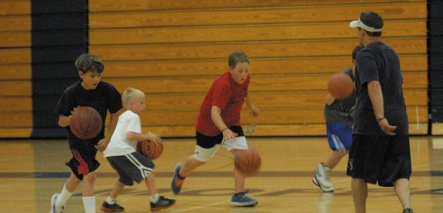 "Campers take part in a ball-handling drill Tuesday at Moffat County High School basketball camp. At right, boys basketball coach Eric Hamilton directs the drill. The three-day camp focused on fundamental skills and teaching younger players ""how to practice on their own,"" Hamilton said."