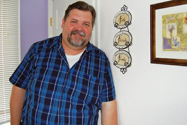 Bruce Cummings leans against a wall decoration emphasizing faith, friends and family in the offices at Advocates-Crisis Support Services. Cummings, who has been involved with the organization for five years, is starting a new program called Mens Voices Against Violence and hosted the first meeting last night.