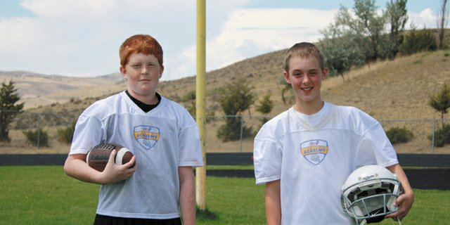  Justin Dugan (left) and Cole White attended the USA Football Academy to help prepare for their first season of 11-man football as seventh graders at Craig Middle School. Dugan and White said the camp improved their respective games and has given them a leg up on competition before the CMS season starts.
