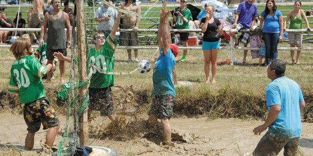 Players contest a ball at the net during the Craig Chamber of Commerce's Mud Splash mud volleyball tournament Saturday at Loudy-Simpson Park. The team from Jack's Bumpers, right, won the match and were the runners-up in the annual event.