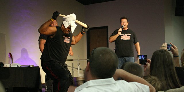 Former Chicago Bear Jerome King attempts to break a baseball bat over his head during a performance by the John Jacobs Next Generation Power Force on Sunday at New Creation Church in Craig. More than 400 people attended the two performances put on by the Power Force.