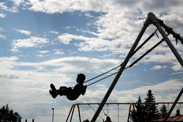 An East Elementary School student swings in front of bright clouds Monday on the first day of school during recess.