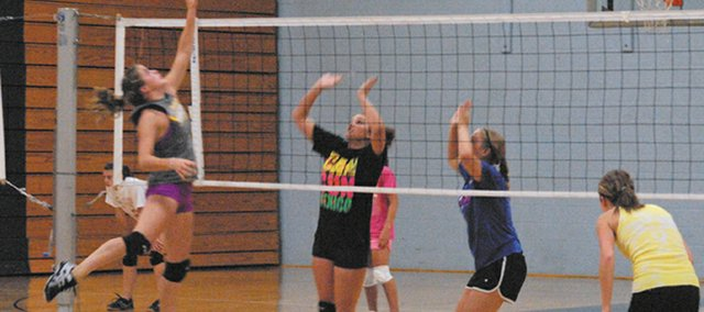 Moffat County High School sophomore Lauren Samuelson goes up to hit the ball over the net against defenders at a practice this summer. The volleyball team begins its season today at Glenwood Springs High School.