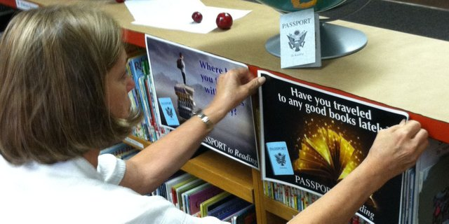 Librarian Bonnie Thompson, of Sunset Elementary School, hangs a sign and sets up a display in anticipation of the Passport to Reading program. The program, for fourth and fifth graders, aims to encourage students to read books from different genres, and not just ones they are comfortable with. Upon reading books, students receive stamps in their &quot;passports.&quot; 