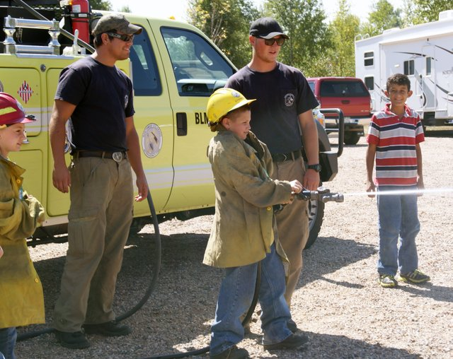 Connor Winn, of Sunset Elementary, takes his turn to spray the hose, as firefighters Hawk Fick, left, and Alex Farinetti of the Craig Bureau of Land Management look on. Fifth graders from Sunset and East Elementary schools took part in an overnight outdoor education experience Thursday and Friday at Yampa River State Park.