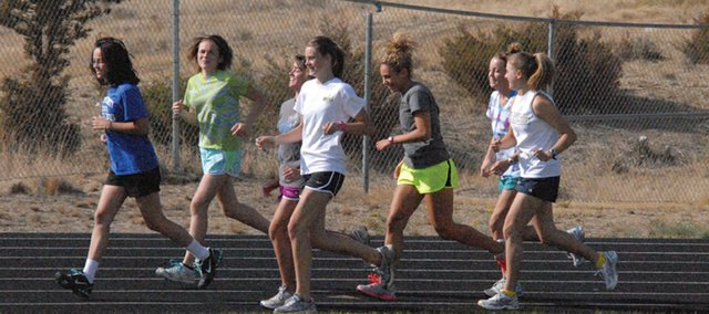 Members of the girls cross country team warm up on the track Monday afternoon at Moffat County High School. The team took sixth place at the Liberty Bell Cross Country Invitational Friday, racing against all Class-4A schools.