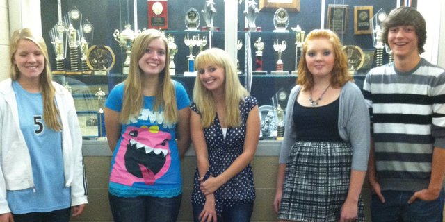 Members of the Moffat County Speech and Debate team, from left, senior Rose Howe, sophomore Treann Quick, sophomore Tiffany Lingo, junior Laurie Cotten and senior Matt Balderston, stand in front of a trophy case holding the teams awards from over the years.