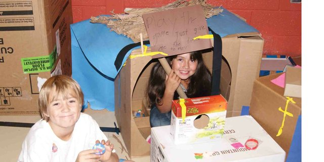 Sunset students sit inside and next to the game they created during the Cardboard Challenge on Friday.