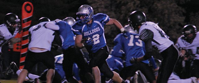 Michael Samuelson breaks through the line during the first half of Friday night's game vs. Summit at the Bulldog Proving Grounds. The Bulldogs used dominant defense and a potent running attack to win, 33-0.