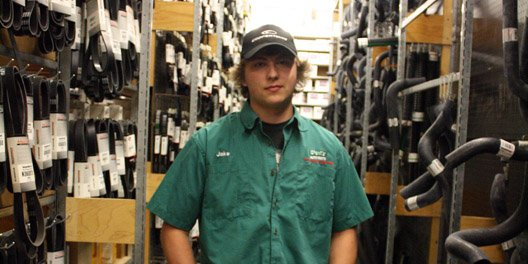 Jacob Baron, retail services specialist at O'Reilly Auto Parts, stands in an aisle of hoses and belts in the back of the store. Baron enjoys reading philosophy books, contrary to his lifestyle as a mechanic and automotive student at Colorado Northwestern Community College.