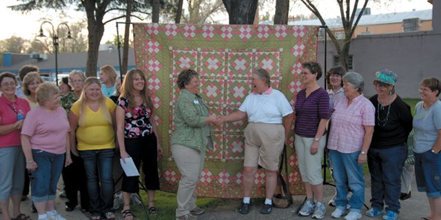 Lorrae Moon, center left, shakes hands with Mary Nelson, of the Yampa Valley Ladies Golf Association, last spring while presenting the quilt as a donation to the association. The quilt garnered $1,266 in the form of donations for the Moffat County Cancer Society this year. The ladies golf association accepted donations for chances to win the quilt.