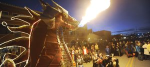 Steamboat Springs resident Charlie Holthausen's dragon spits fire during the Downtown Halloween Stroll on Wednesday night in Steamboat Springs. During breaks from trick-or-treating, kids lined up for the chance to make the 35-foot fire-breather come alive.